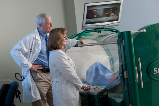 Doctors overseeing a patient getting treatment in a hyperbaric chamber.