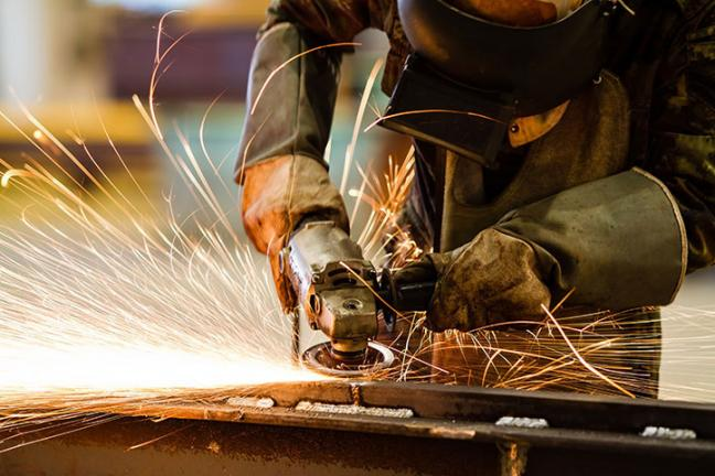 Industrial worker grinding metal with sparks flying