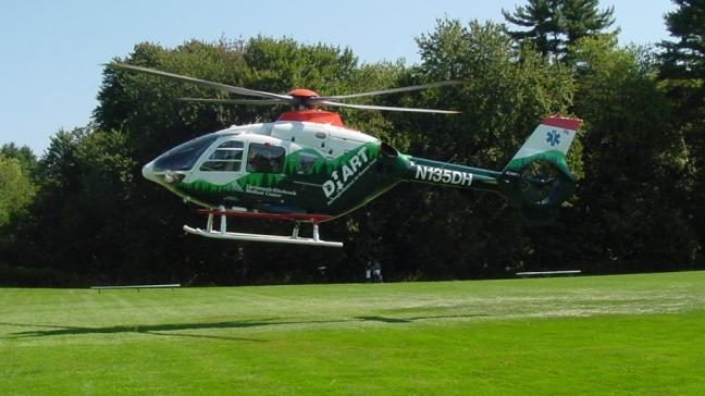 A DHART helicopter lands on a field.