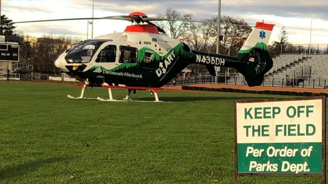 A DHART helicopter is parked on a sports field.