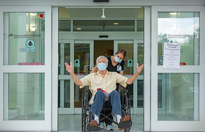 Discharged, masked patient at East Entrance in wheelchair with masked nurse.